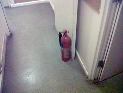 I am sure everyone has seen this one countless times; fire door held open by a fire extinguisher.  When two (2) doors and two (2) extinguishers are involved, it is not unusual for the extinguisers to be put back in the wrong place; i.e. under the wrong signage for the type and use.